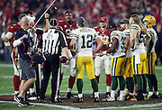 NFL back judge Keith Ferguson (61), the Arizona Cardinals, and the Green Bay Packers look on as referee Clete Blakeman (34) flips the coin for an overtime period during the Arizona Cardinals NFL NFC Divisional round playoff football game against the Green Bay Packers on Saturday, Jan. 16, 2016 in Glendale, Ariz. The Cardinals won the game in overtime 26-20. (©Paul Anthony Spinelli)