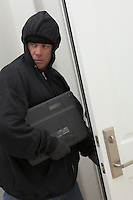 Burglar stealing laptop