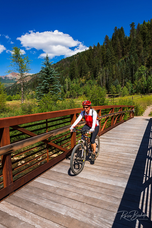 Mountain biker crossing a bridge on the Galloping Goose Trail, Uncompahgre National Forest, Colorado USA (MR)