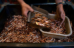 Shell casings are cleaned and polished by special machines before being loaded with live rounds at the FN Herstal weapons fabrication plant near Liege, Belgium.