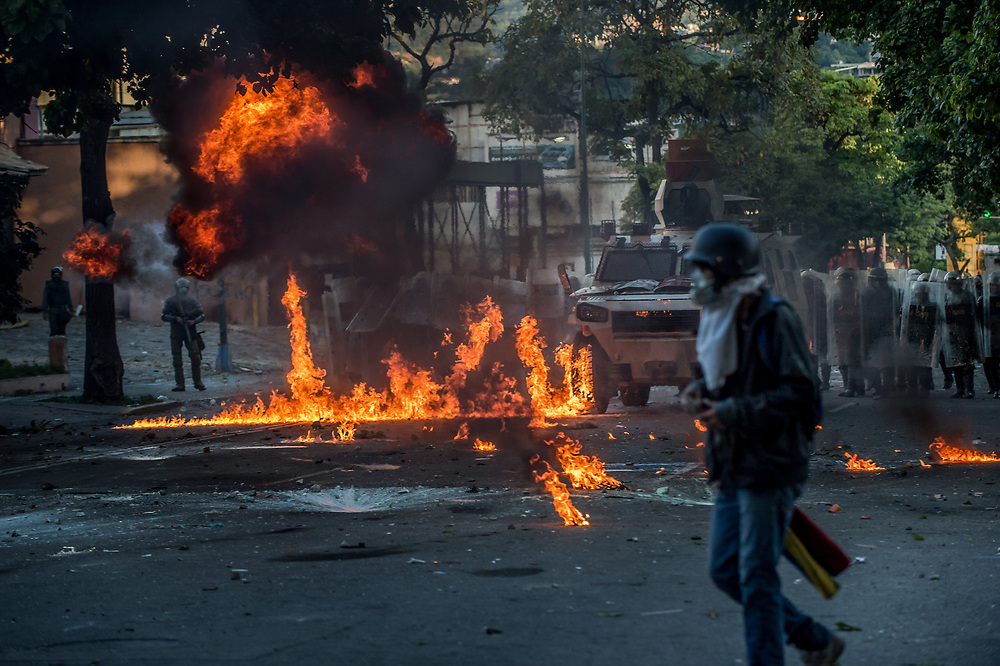 CARACAS, VENEZUELA - JULY 26, 2017: A Molotov cocktail thrown by members of La Resistencia explodes at the feet of National Guard soldiers, during an anti-government protest to demand that the National Constituent Assembly election scheduled for Sunday, July 30th be cancelled. The political opposition called for a 48 hour national strike on July 26th and 27th, and for their supporters to close businesses, not go to work, and instead create barricades to block off their streets.  Opposition controlled areas of the country were completely shut down.  The strike was called as part of the opposition's civil resistance movement - that began on April 1st, to protest against the Socialist government's attempt to elect a new assembly that will have the power to re-write the constitution, and their opposition to the Socialist's continued threats to Venezuelan Democracy.  PHOTO: Meridith Kohut for The New York Times