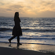 a woman is walking along the beach during sunset