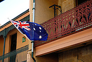 "Old terraced houses converted to shops, with ""iron lace"" and Australian Flag. The Rocks, Sydney, Australia"