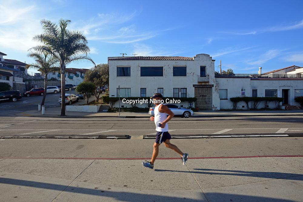 Mature man running in Santa Cruz boardwalk, California.