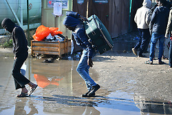 © Licensed to London News Pictures. 23/10/2016. Calais, France. Migrants carry suit cases through the camp as preparations begin for the demolition of the migrant camp in Calais, France, known as the 'Jungle'. French authorities have given an eviction order to thousands of refugees and migrants living at the makeshift living area of the French coast. Photo credit: Ben Cawthra/LNP