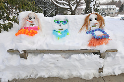 Childs Creative Artwork, Plastic Sculptures. Funny People made from carrot sticks, coal, lays, sunglasses and built into a Snow Covered Park Bench. Hamden CT Condo Courtyard.