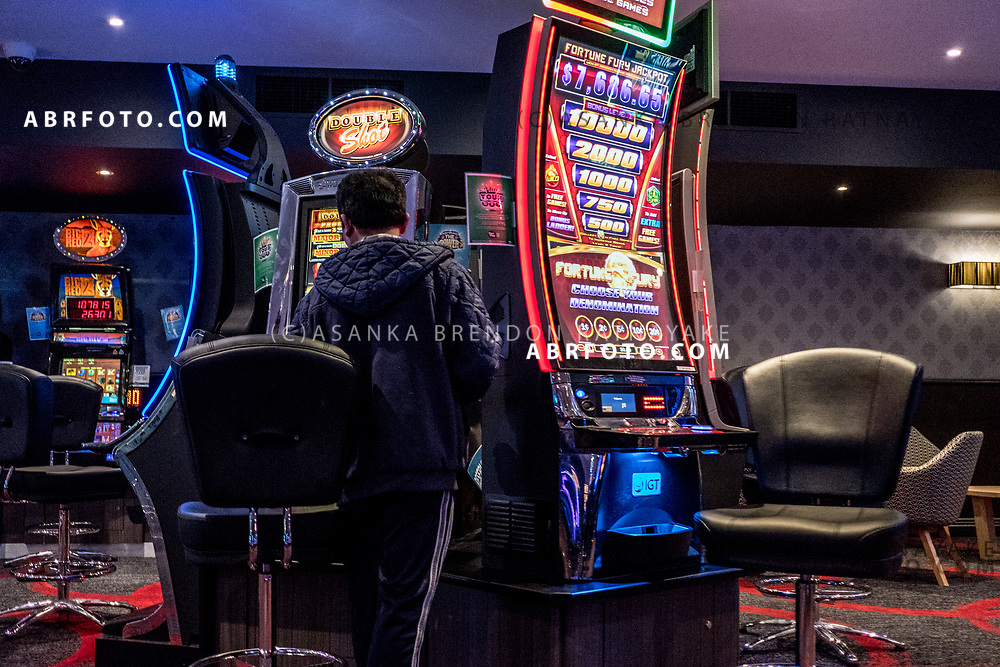 A pokie player plays a poker machine at a gaming venue in the western suburbs of Melbourne on the 26th of March 2018. Asanka Brendon Ratnayake for The New York Times.