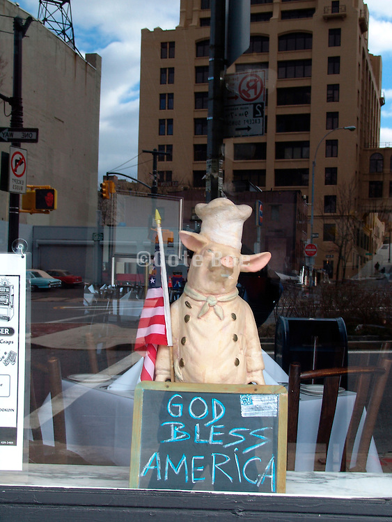 A display in a restaurants window of piggy cook with an American flag.