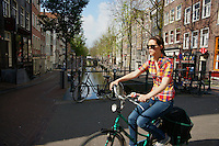 A girl rides a bike past a canal in Amsterdam one of the most bicycle friendly cities in the world.