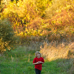 A nine year old boy plays in a field at Elmwood Farm in Hopkinton, Massachusetts. Fall.