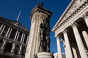 First World War memorial soldier beneath the Bank of England (L) and the columns of Royal Exchange. The tall and solid Corinthian pillars of the 3rd Royal Exchange built in 1842 by Sir William Tite. Looking upwards towards a memorial that commemorates the dead from the First World War of 1914-18 between the converging pillars of the Cornhill Exchange building and beyond, to the famous Bank of England in the City Of London, the financial district, otherwise known as the Square Mile. The Bank of England (formally the Governor and Company of the Bank of England) is the central bank of the United Kingdom and the model on which most modern central banks have been based. It is wholly owned by the Treasury Solicitor on behalf of the Government, with independence in setting monetary policy.
