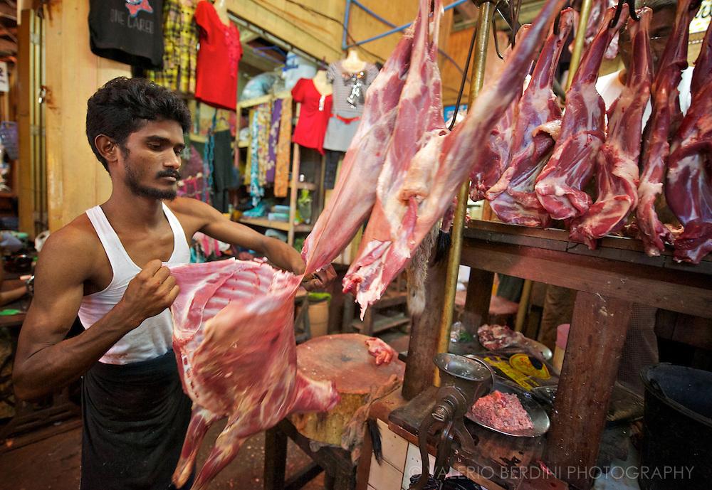 A butcher cuts a lamb in a Rangoon food market.