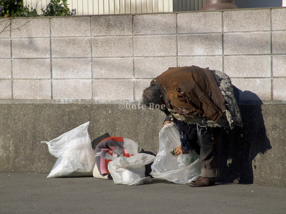 a Japanese homeless person warming himself in the sun