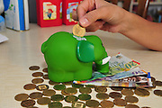 Saving coins in a piggy bank