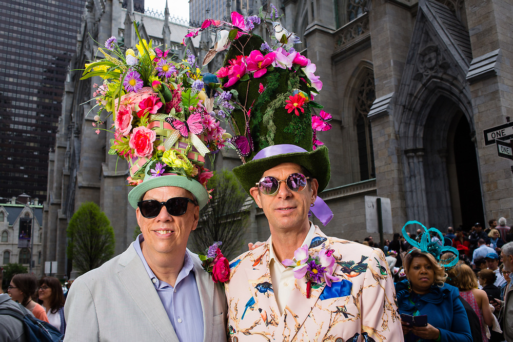 New York, NY - 21 April 2019. Two men, both wearing tall floral hats, and one  wearing a suit with a fabric decorated with birds, at the Easter Bonnet Parade and Festival on New York's Fifth Avenue.