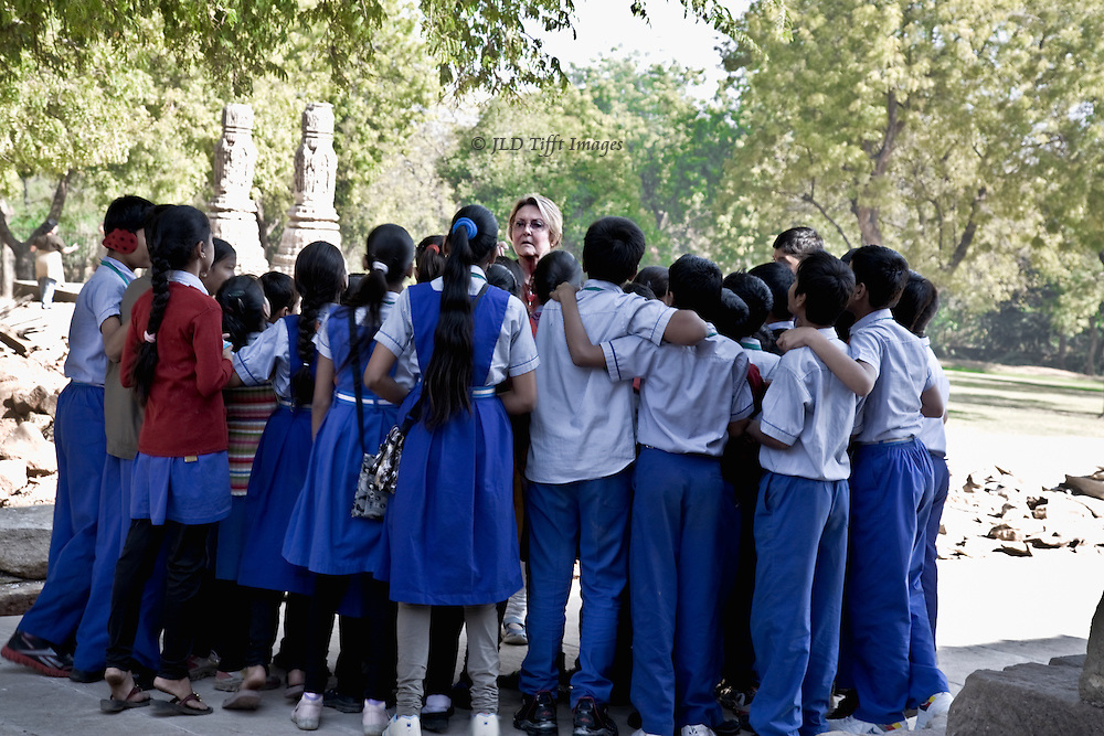 Blonde Western tourist in discussion with a crowd of Indian adolescents on a school visit about taking their photograph.