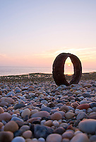 New York, Long Island - sun through the rusty ring on the beach at sundown.