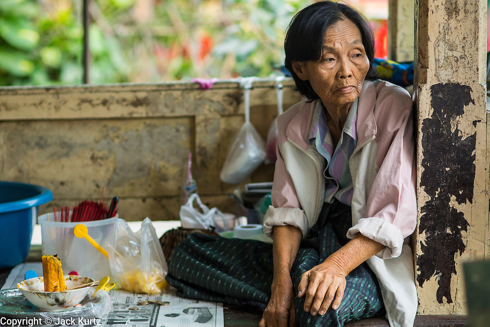 04 JANUARY 2012 - BANGKOK, THAILAND:  A woman who sells fish food to Thais hoping to make merit by feeding fish and pigeons waits for customer at Wat Mahabut in eastern Bangkok. The temple was built in 1762 and predates the founding of the city of Bangkok. Just a few minutes from downtown Bangkok, the neighborhoods around Wat Mahabut are interlaced with canals and still resemble the Bangkok of 60 years ago. Wat Mahabut is a large temple off Sukhumvit Soi 77. The temple is the site of many shrines to Thai ghosts. Many fortune tellers also work on the temple's grounds.   PHOTO BY JACK KURTZ