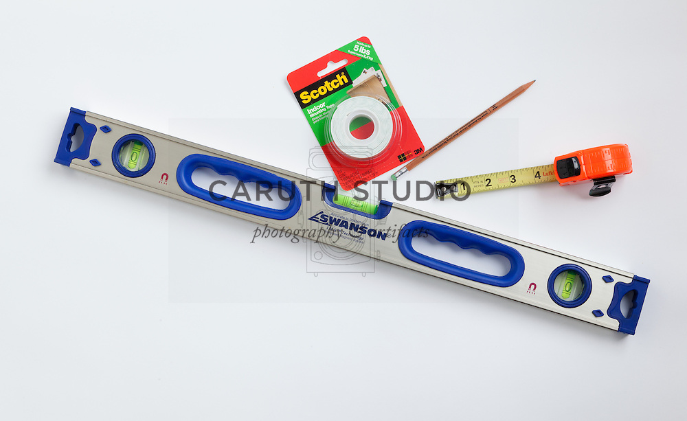 Tools for mounting wall trim: level, mounting tape, measuring tape, and pencil
