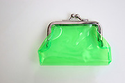 Small green purse for change and coins on white background