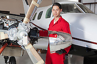 Portrait of young aeronautic engineer standing in front of an airplane propeller