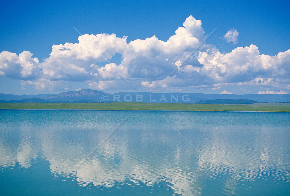 Cloud bank over the Taos mountain range and the calm blue water of Lake isabella in the New Mexico high desert