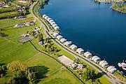 Nederland, Gelderland, Maasbommel, 27-05-2013;<br /> Drijvende woningen in het water van recreatiegebied De Gouden Ham, onderdeel van de rivier de Maas.<br /> De recreatiewoningen maken onderdeel uit van een complex van buitendijks gebouwde tweede huizen, die (gaan) drijven bij hoog water, de woningen zijn bevestigd aan meerpalen om verschillen in waterhoogte op te vangen.<br /> Floating houses in the river Maas, rise and fall with the water; <br /> luchtfoto (toeslag op standaardtarieven);<br /> aerial photo (additional fee required);<br /> copyright foto/photo Siebe Swart.
