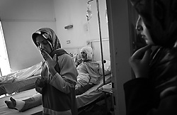 "Alameda Ghaith, a student, stands by her father Mohammed Ghaith's hospital bedside after their home was hit by a rocket from an Israeli helicopter earlier in the week, in Tyre, Lebanon, July 27, 2006. <br /> Her mother and sister, who was set to be married the following month, died instantly. She asked, ""Do we look like Hezbollah fighters to you?"""