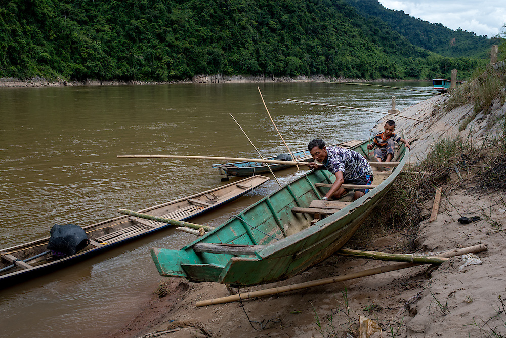 A fisherman and his son repair their boat along the Mekong river at the village of Khoc Kham. The village is not connected to the main electrical grid and many residents operate their own turbines to power lights and sometimes small appliances.
