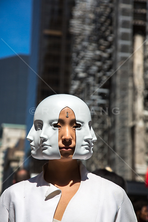 man in a mask with many faces on the street in New York City