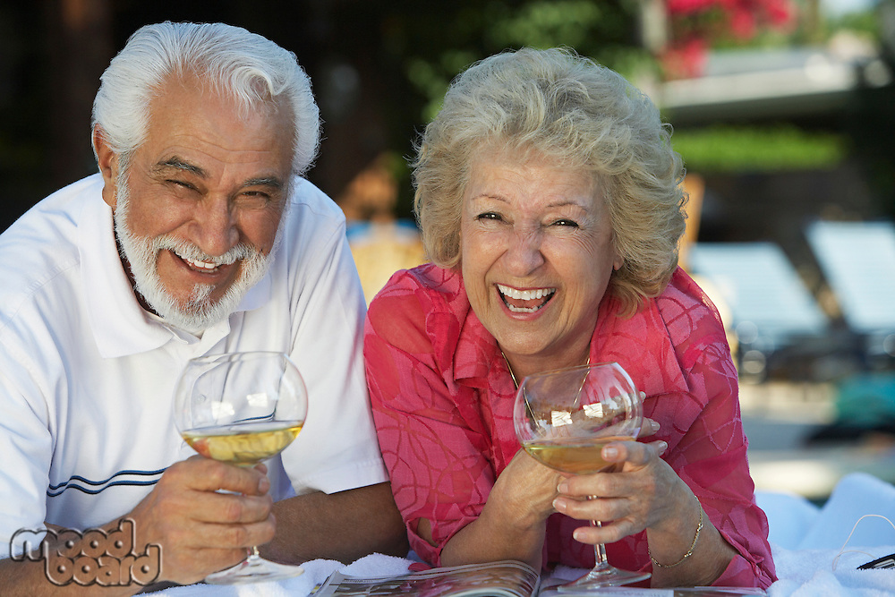 Portrait of senior couple relaxing in garden with wine and laughing