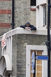 "© Licensed to London News Pictures . 11/06/2013 . London , UK . A man wearing a black face mask on the roof above the entrance where police surround a former police station on 40 Beak Street , Soho this morning (11th June) which has been occupied by organisers as a base for today's "" Stop G8 "" anti capitalist protest . Demonstrations in London today (Tuesday 11th June 2013) ahead of Britain hosting the 39th G8 summit on 17th/18th June at the Lough Erne Resort , County Fermanagh , Northern Ireland , next week . Photo credit : Joel Goodman/LNP"