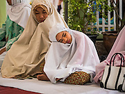 06 JULY 2016 - BANGKOK, THAILAND:  Women and girls wait for Eid services to start at Ton Son Mosque in the Thonburi section of Bangkok. Eid al-Fitr is also called Feast of Breaking the Fast, the Sugar Feast, Bayram (Bajram), the Sweet Festival or Hari Raya Puasa and the Lesser Eid. It is an important Muslim religious holiday that marks the end of Ramadan, the Islamic holy month of fasting. Muslims are not allowed to fast on Eid. The holiday celebrates the conclusion of the 29 or 30 days of dawn-to-sunset fasting Muslims do during the month of Ramadan. Islam is the second largest religion in Thailand. Government sources say about 5% of Thais are Muslim, many in the Muslim community say the number is closer to 10%.       PHOTO BY JACK KURTZ