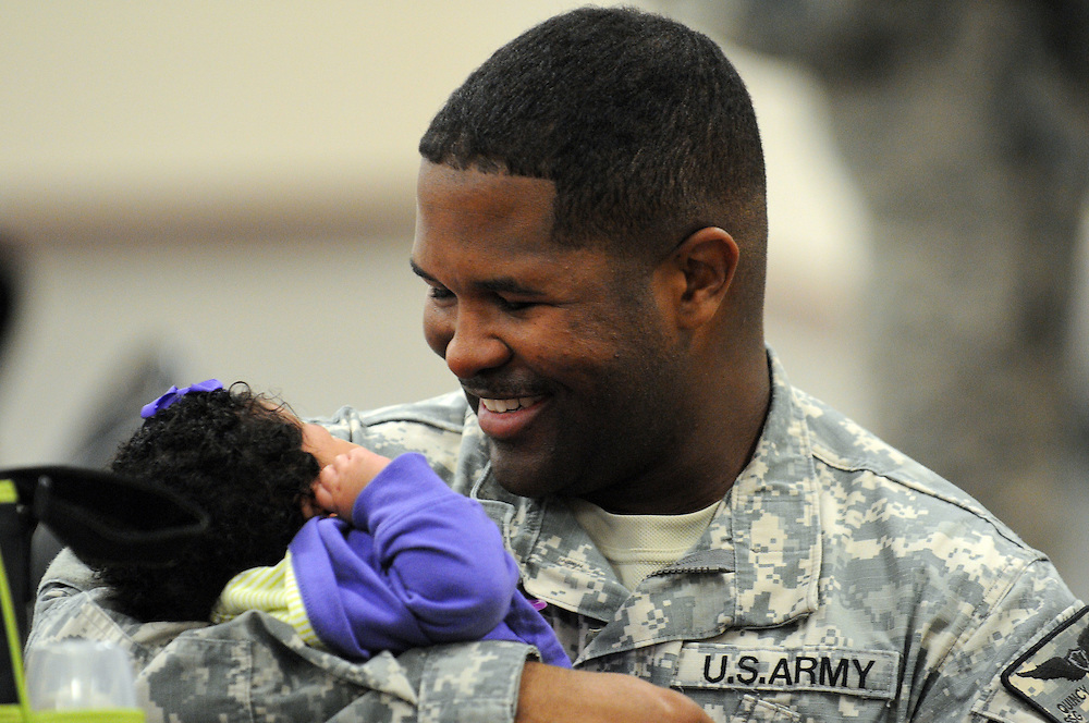 Staff Sgt. Quincy Duplessis hold his 3-month-old daughter Jordyn Gleen for the first time Tuesday night at Camp Shelby after returning from Iraq. Duplessis' fiance Tiajuanda Gleen found out she was pregnant one month after he was deployed. Although unable to attend the birth, Duplessis was digitally present via Skype. Duplessis was one of two bus loads of the 185th Aviation division of the Mississippi National Guard who returned home from Iraq to Camp Shelby. Bryant Hawkins/ Hattiesburg American