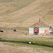 Kyrgyz woman washing hands in street, Pshart Valley, Pamir plateau, Tajikistan