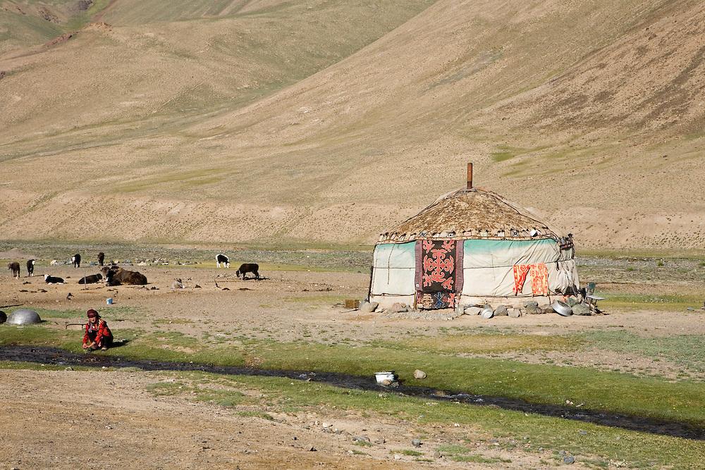 Kyrgyz woman washing hands in street, Pshart Valley, Pamir plateau, Tajikistan