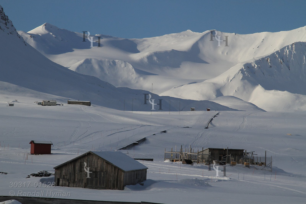 Sheds and dog kennel at the international science village of Ny-Alesund are dwarfed by the snowy mountains of Spitsbergen island in April at Kongsfjorden; Svalbard, Norway.