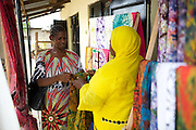 Salma Likupila (right) talking to a customer in her shop near Picha ya Ndege in Tanzania.<br /> <br /> Salma set up and now runs a Batik business, making and selling Batik as well as towels and bed linen.<br /> <br /> She attended MKUBWA enterprise training run by the Tanzania Gatsby Trust in partnership with The Cherie Blair Foundation for Women.