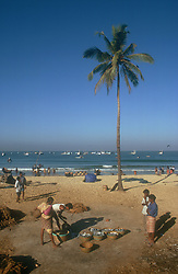 Beach scene in Goa; India; with fishermen and women; baskets of fish and fishing nets,