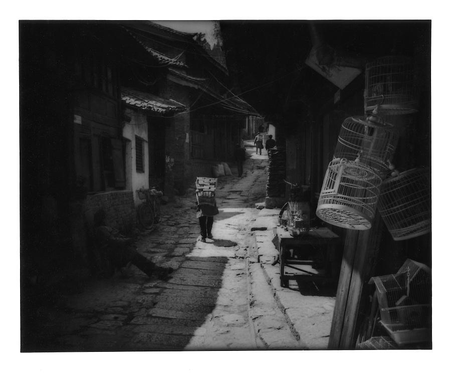 Naxi woman struggling beneath her load through a backstreet.  Lijiang, Yunnan, China.  1997