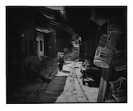 Naxi woman struggling beneath her load through a backstreet.  Lijiang, Yunnan, China.  1997