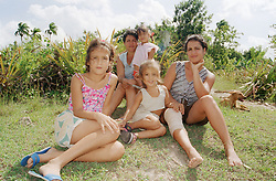 Women and children sitting by a field on a farm near Banes; Cuba,