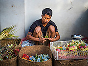 11 OCTOBER 2016 - UBUD, BALI, INDONESIA: A man makes floral offerings for the temple in the Ubud market.The morning market in Ubud is for produce and meat and serves local people from about 4:30 AM until about 7:30 AM. As the morning progresses the local vendors pack up and leave and vendors selling tourist curios move in. By about 8:30 AM the market is mostly a tourist market selling curios to tourists. Ubud is Bali's art and cultural center.      PHOTO BY JACK KURTZ