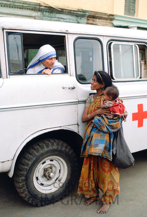 Mother Teresa talking with a poor woman and her child from a Red Cross minibus in Calcutta, India
