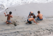young boys playing by the shore