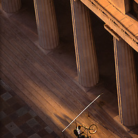 Bicycle messinger making a delivery to Miami Dade Court House on Flagler Street in downtowm Miami.  Shot from a high angle at with golden sunset light.