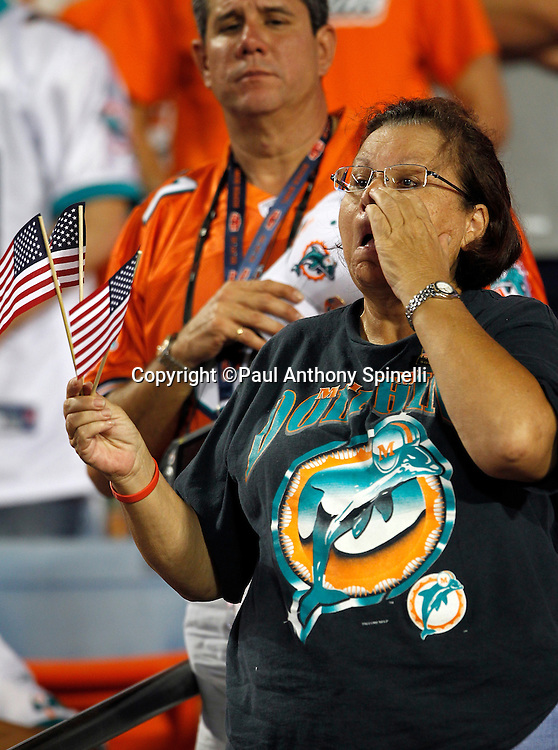 A Miami Dolphins fan holds American flags and wipes away a tear during the playing of the National Anthem at the NFL week 1 football game against the New England Patriots on Monday, September 12, 2011 in Miami Gardens, Florida. The Patriots won the game 38-24. ©Paul Anthony Spinelli