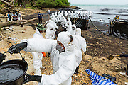 """30 JULY 2013 - KOH SAMET, RAYONG, THAILAND: A """"bucket brigade"""" of workers removes oil from Ao Prao beach on Koh Samet island. About 50,000 liters of crude oil poured out of a pipeline in the Gulf of Thailand over the weekend authorities said. The oil made landfall on the white sand beaches of Ao Prao, on Koh Samet, a popular tourists destination in Rayong province about 2.5 hours southeast of Bangkok. Workers from PTT Global, owner of the pipeline, and up to 500 Thai military personnel are cleaning up the beaches. Tourists staying near the spill, which fouled Ao Prao beach, were evacuated to hotels on the east side of the island, which was not impacted by the spill. PTT Global Chemical Pcl is part of state-controlled PTT Pcl, Thailand's biggest energy firm.      PHOTO BY JACK KURTZ"""