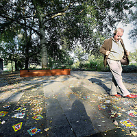Nederland, Amsterdam , 3 oktober 2011..Henk van de Belt, ooggetuige van de Bijlmerramp uit 1992 veegt bladeren weg bij de tegels van het monument van de Bijmerramp..Op de achtergrond de boom die alles heeft gezien..Foto:Jean-Pierre Jans