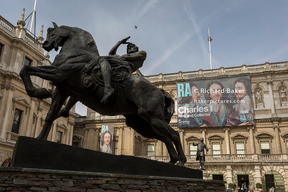 The sculpture of a heroic male figure on horseback entitled Physical Energy by artist George Frederick Watts in the Annenberg Courtyard of Burlington House, the Royal Academy in Piccadilly where the exhibition entitled 'Charles 1, King and Collector' is showing, on 6th April 2018, in London, England. This is a new cast of the original that was first exhibited outside the RA in 1904 and is an allegory of the human need for new challenges, of our instinct to always be scanning the horizon and the future. King Charles I amassed one of the most extraordinary art collections of his age, acquiring works by some of the finest artists of the past – Titian, Mantegna, Holbein, Dürer – and commissioning leading contemporary artists such as Van Dyck and Rubens. Following the his execution in 1649, the king's collection was sold off and scattered across Europe. Many works were retrieved during the Restoration, others now form the core of museums such as the Louvre and the Prado. This show reunites the greatest masterpieces of this magnificent collection for the first time.